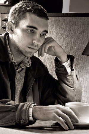 Man sits in a coffeehouse in quiet contemplation