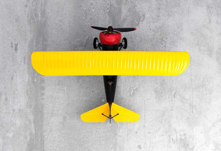 fixed wing aircraft: Upside view of a yellow and black biplane on ground.