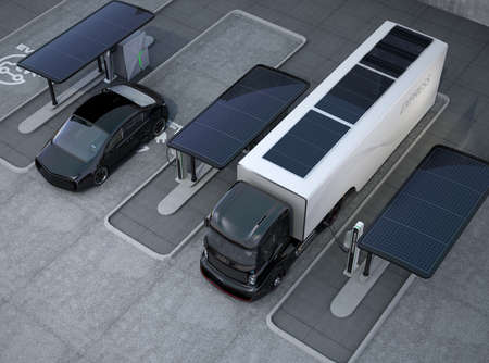 Hybrid electric truck and white electric car in charging station 免版税图像