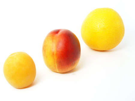 three fruits apricot nectarine and orange in line on white background photo
