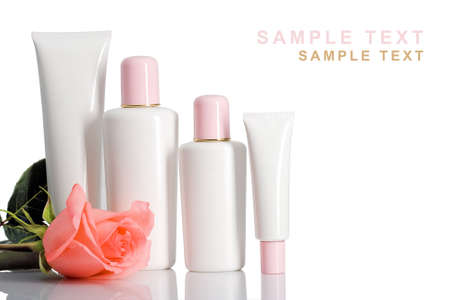 standing cosmetic bottles and tubes on white with rose and text space Stock Photo