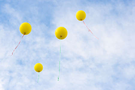 copy sapce: four yellow baloons rising to the blue sky, copy sapce fo text