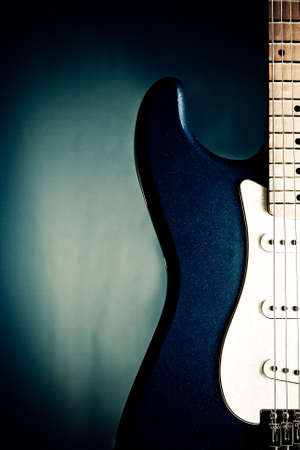 closeup blue electric guitar with blue background photo