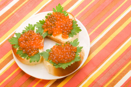 sandwiches with butter green parsley and red salmon caviar on the plate photo