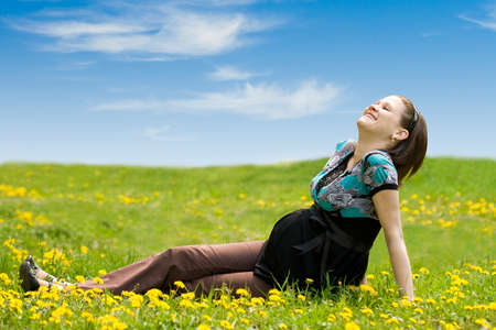 pregnant woman on green grass and blue sky background