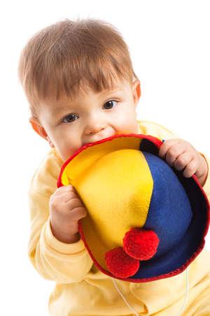 nibble: baby boy gnaw clown hat, portrait on white Stock Photo