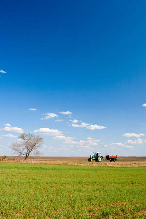green tractor working on spring fields Stock Photo - 4992307
