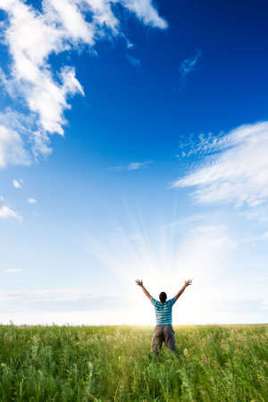 young man standing over rising sun Stock Photo