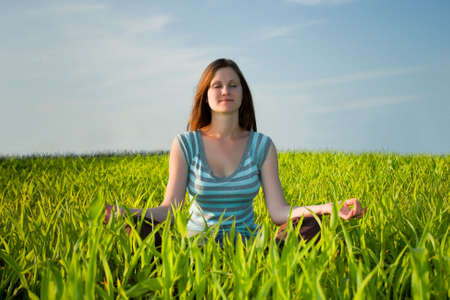 woman meditating in green field photo