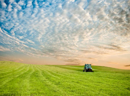 tractor in the field under sunset clouds photo