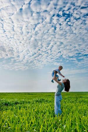 mamma e figlio: donna azienda ragazzo, che satnding sul campo verde