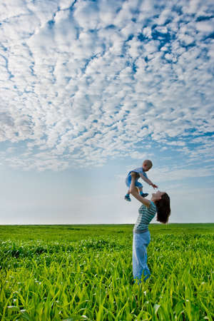 mother and son: woman holding boy,  they satnding on green field
