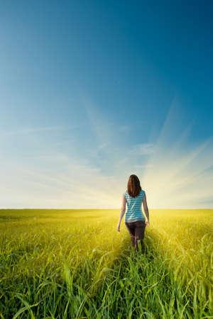 away: woman walking away on green field