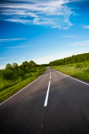 nowhere: black highway road under blue skies Stock Photo