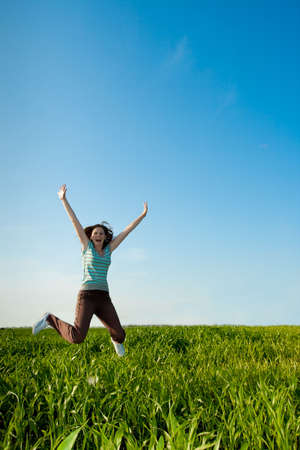 young woman jumping on geen field photo