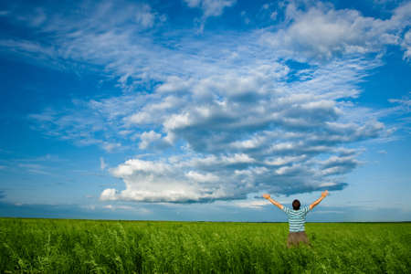 man in summer field under clouds on blue skies Stock Photo - 5772977