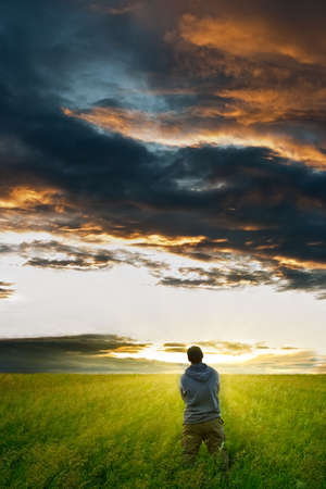 Strom: man under the strom clouds before sunset Stock Photo