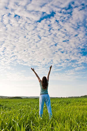 woman rising up hands  in the green  field Stock Photo - 5884209