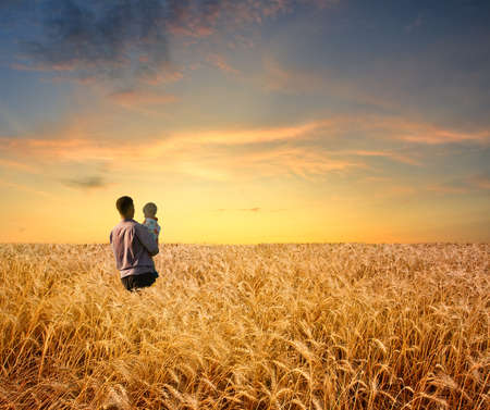 man in wheat field with boy photo