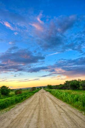 route de saleté au coucher du soleil dans les champs