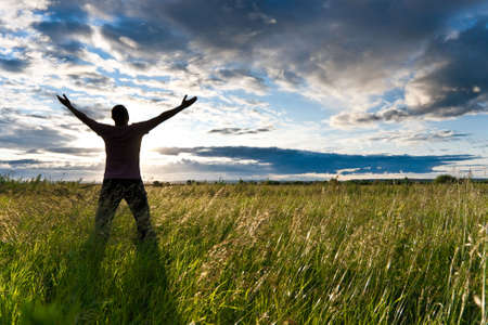 sol naciente: hombre de pie en el campo antes del sol