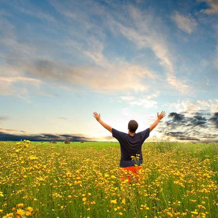 sol naciente: hombre de campo con flores amarillas en virtud de la puesta de sol