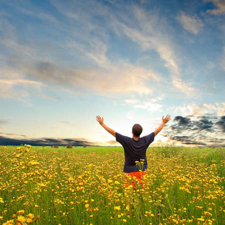 joy of life: man in field with yellow flowers under sunset Stock Photo