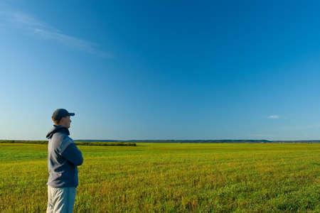 loin: homme debout sur le champ et de loin la recherche
