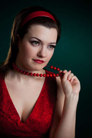 portrait of woman in red touching beads photo
