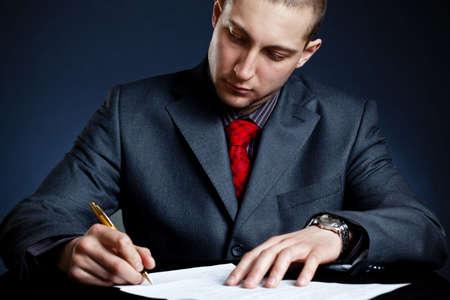 businessman signing documents: businessman signing documents over blue background