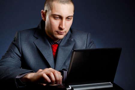 businessman working with  netbook over dark blue photo