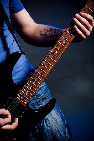 man playing rock on electric guitar photo
