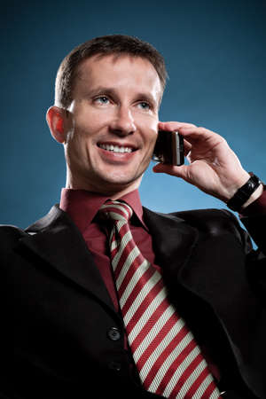 happy businessman calling by phone over blue photo