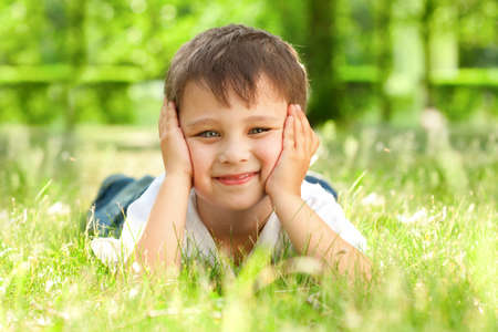 happy little boy laying on the grass in the park photo