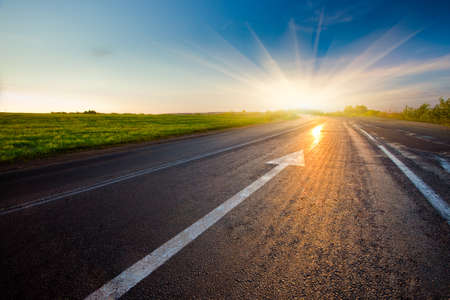 move forward: black asphalt road with arrow to sunset