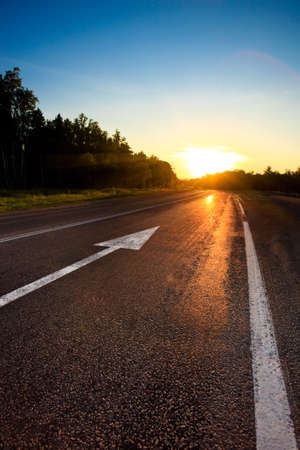 road ahead: road to the sunset with arrow on asphalt