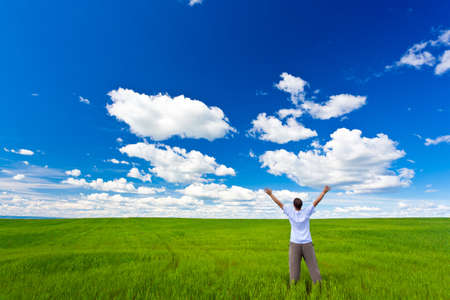 man on field rising up hands under blue skies photo
