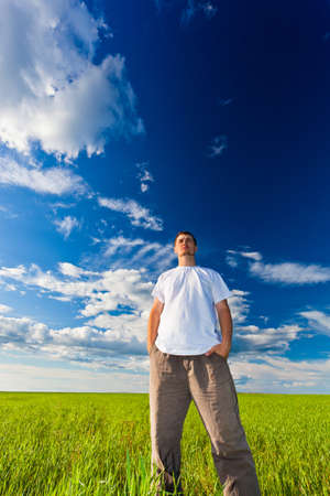 man looking far away standing on green filed Stock Photo - 7832252