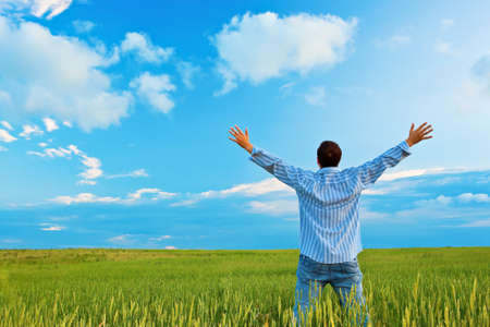 man on green field rising up his hands Stock Photo - 7961859