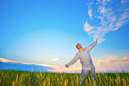 young man relaxing on field before the sunset Stock Photo - 7961871