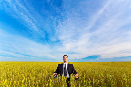 young businessman sitting on field photo