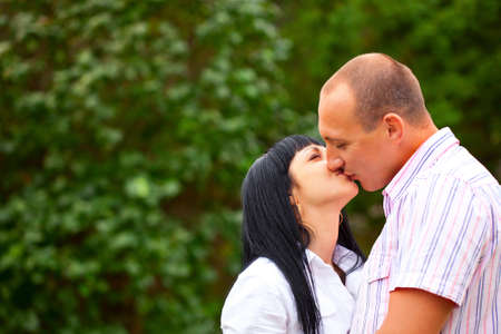 young lovely couple kissing in the park photo