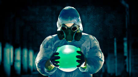 chemical warfare: man in protective costume and respirator holding danger ball