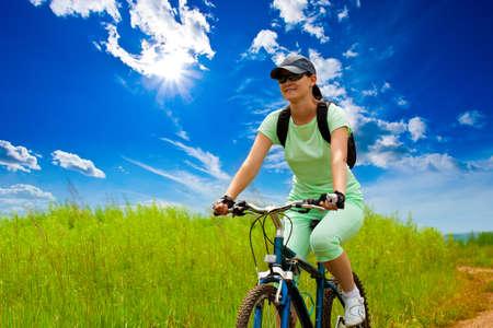 mujer con bicicletas en campo verde bajo cielos azules  Foto de archivo