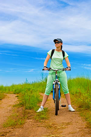 woman with bike on green field under blue skies photo