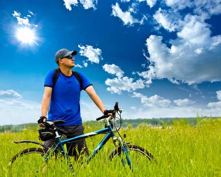 moteros: hombre con bicicletas en campo verde bajo cielos azules