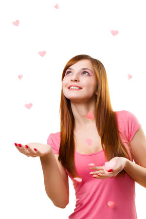 young woman catching paper hearts over white