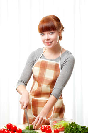 ginger woman wearing apron cooking salad over white photo