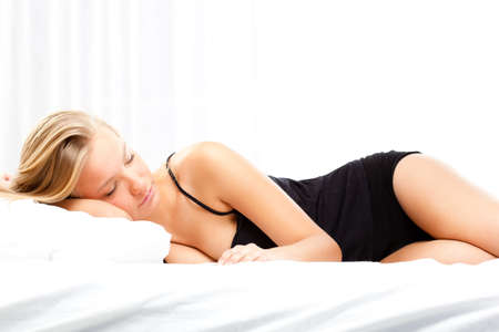 beautiful blonde woman sleeping on white bed photo