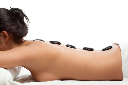 masajes relajacion: mujer bonita, recibiendo una terapia con piedras calientes en el centro de spa en blanco Foto de archivo